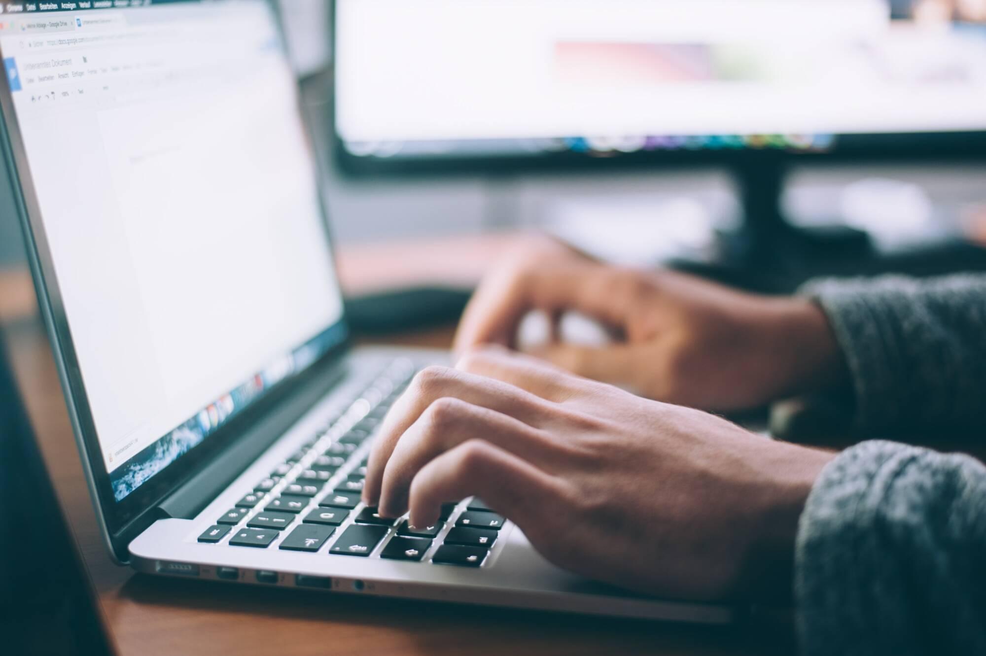 Hände tippen auf Laptop-Tastatur